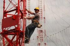 Un ingénieur commence l'ascension des 75m d'une antenne