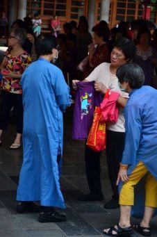 A l'aide de bâtonnets d'encens et de formules magiques, les exorcistes du temple purifient les vêtements ...