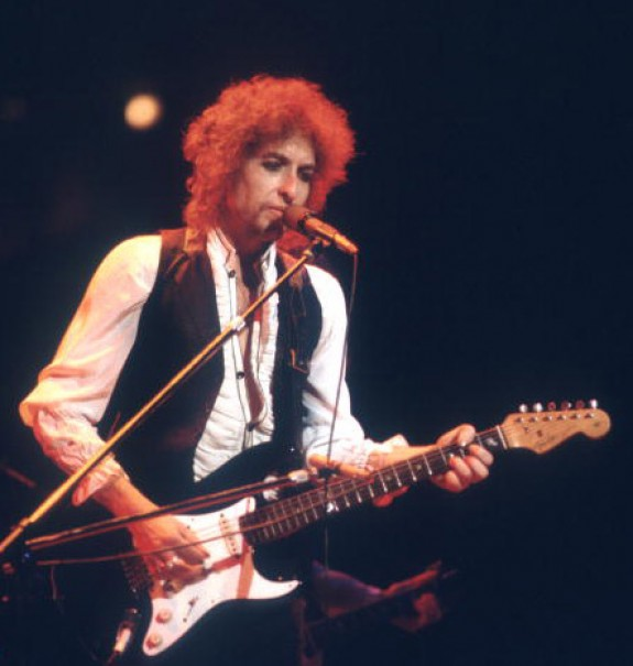 [Picture of Bob Dylan playing electric guitar with band]