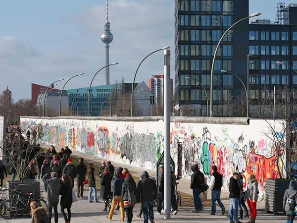 "People stroll at the open air 0.8-mile painted section of the Berlin Wall known as the ""East Side Gallery"" in Berlin"
