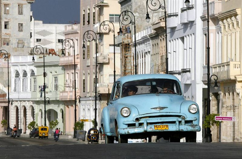 Кубинцы едут на старом автомобиле по набережной