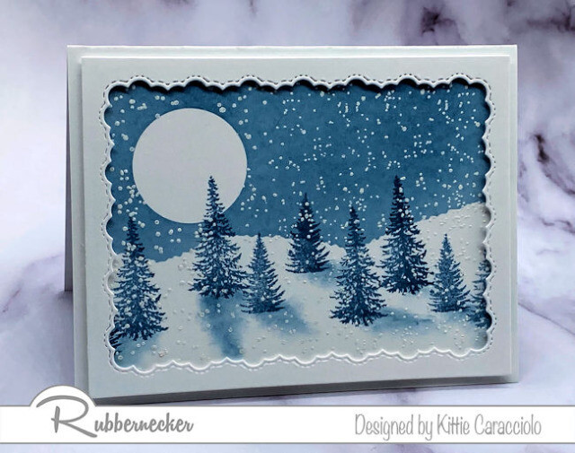 a hand stamped winter pine tree card depicting a winter moonlit scene in shades of blue and white made using new stamps from Rubbernecker