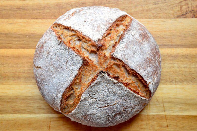 Das Gemischte Roggen Weizen Brot von oben. Das Brot ist bemehlt und wenn man mit dem Finger darüber fährt spürt man den Kreuzschnitt der beim backen leicht aufgegangen ist und auf dem sich kein Mehl befindet.