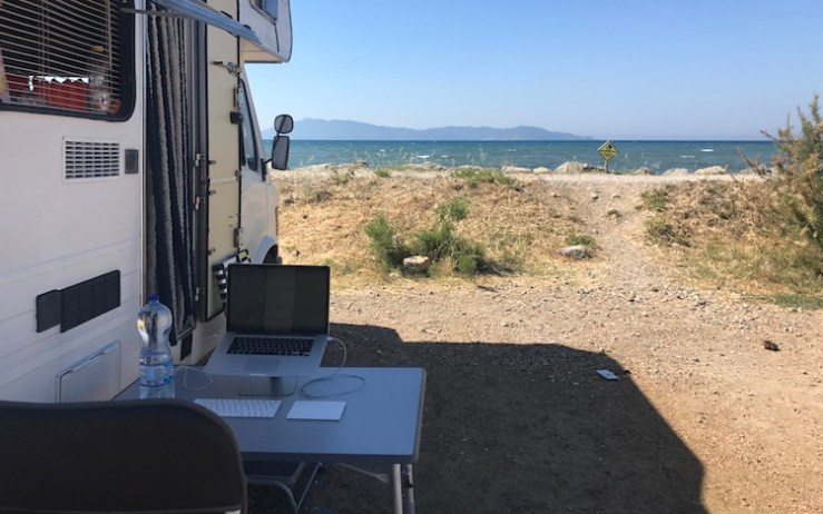 Working outside of the van right next to the sea