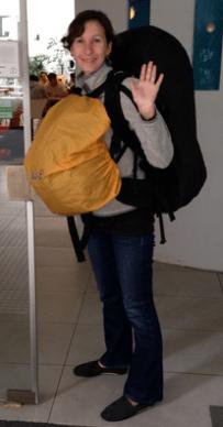 Corinna mit großem Rucksack auf dem Rücken und kleinem auf der Brust