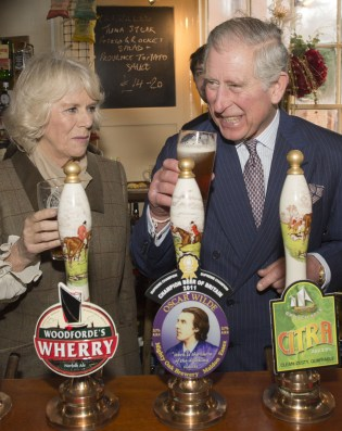 Britain's Prince Charles, The Prince of Wales, (Foreground-R) laughs after pulling a pint of draught beer as Camilla, The Duchess of Cornwall (L) looks on during a visit to The Bell pub in Purleigh on January 29, 2014. AFP PHOTO/POOL/ARTHUR EDWARDS (Photo credit should read ARTHUR EDWARDS/AFP/Getty Images)