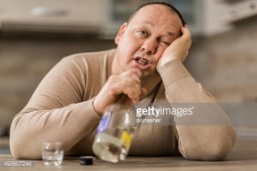 Overweight man sitting drunk at home and holding bottle.