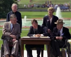 P14777-18 President Bush signs the Americans with Disabilities Act on the South Lawn of the White House. Sharing the dais with the President and he signs the Act are (standing left to right): Rev. Harold Wilkie of Clairmont, California; Sandra Parrino, National Council on Disability; (seated left to right): Evan Kemp, Chairman, Equal Opportunity Commission; and Justin Dart, Presidential Commission on Employment of People with Disabilities. Mrs. Bush and Vice President Quayle participate in the Ceremony. 26 July 1990 Photo credit: George Bush Presidential Library and Museum