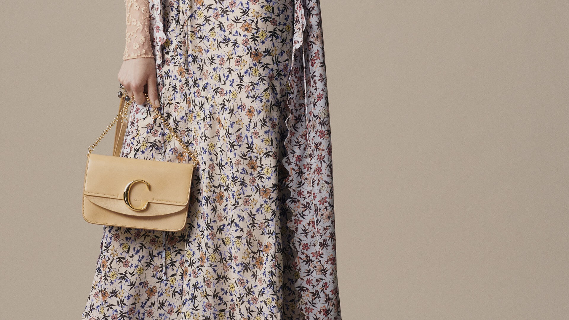 The Chloé C Clutch in faded yellow held by Model dressed in Spring19 Collection
