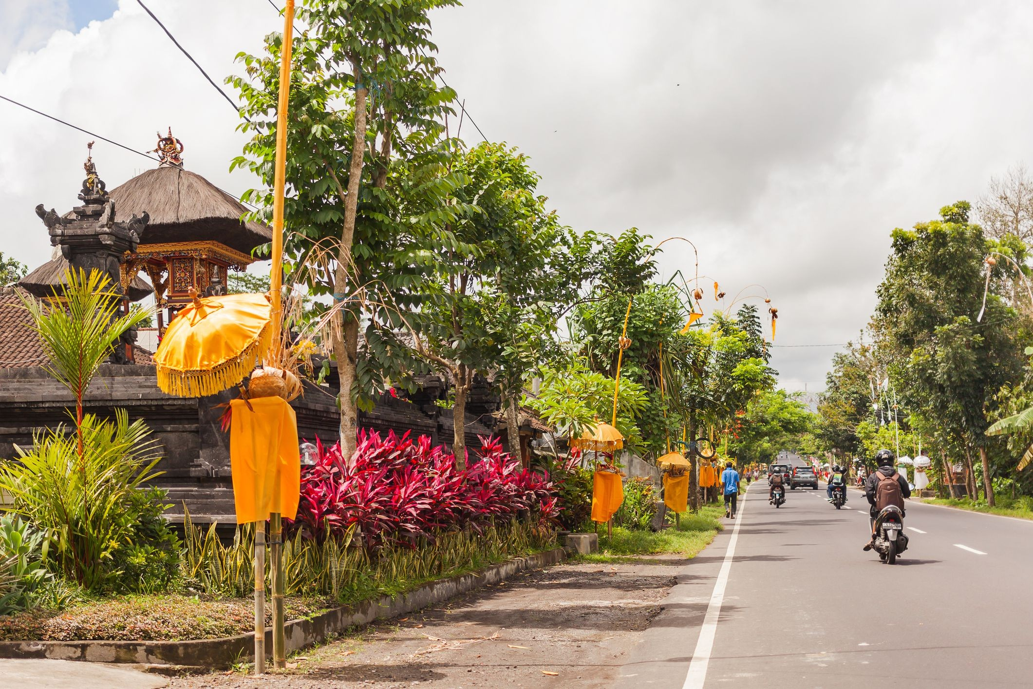 Religious decoration near houses on street Road traffic in sunny day Ubud Bali