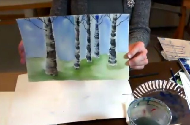Artist holding watercolor painting of birch trees