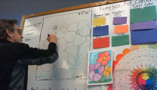 Teaching artist stands in front of a whiteboard with a drawing of flowers.