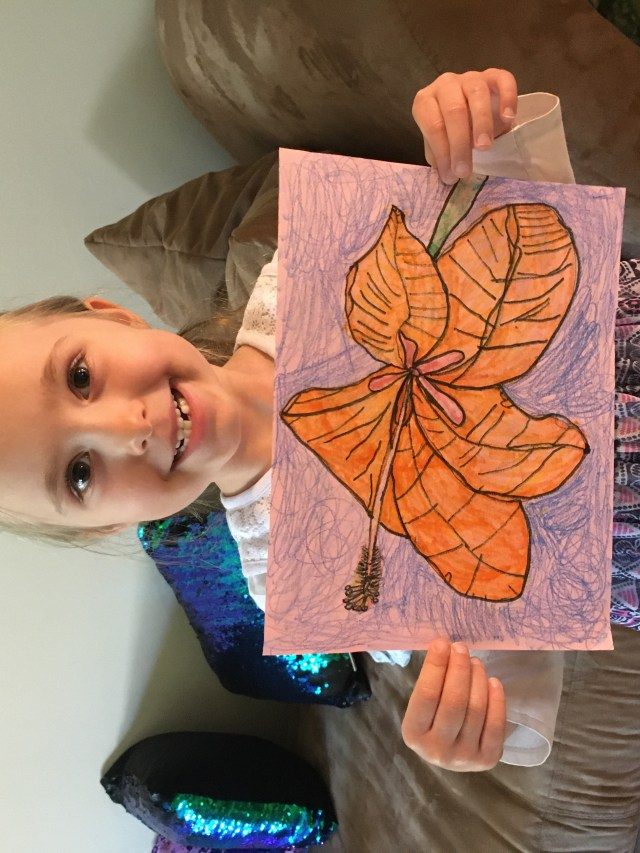 Young girl holding up her drawing of a large orange flower