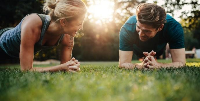 Fitness pár táhnoucí se venku v parku. Mladý muž a žena spolu cvičí ráno.