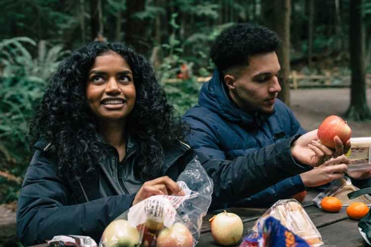 man and woman eating fruits