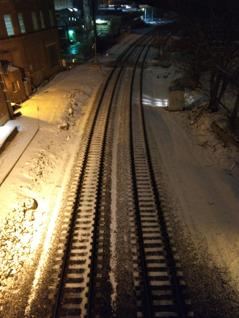 Snowy railroad buildings at night.