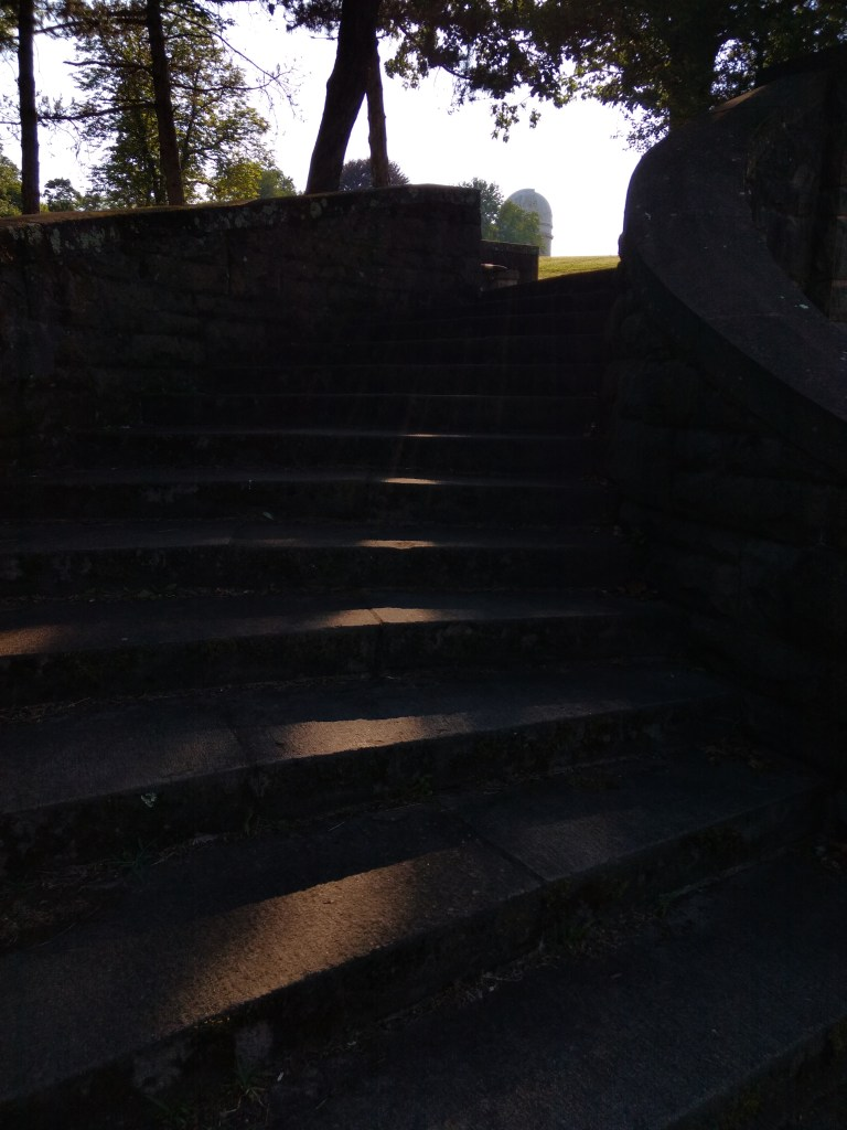 A sliver of light on concrete stairs with an observatory at the top of the steps