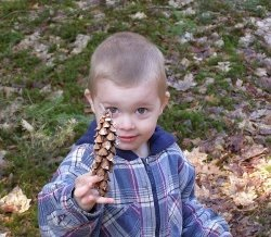 child with pine cone
