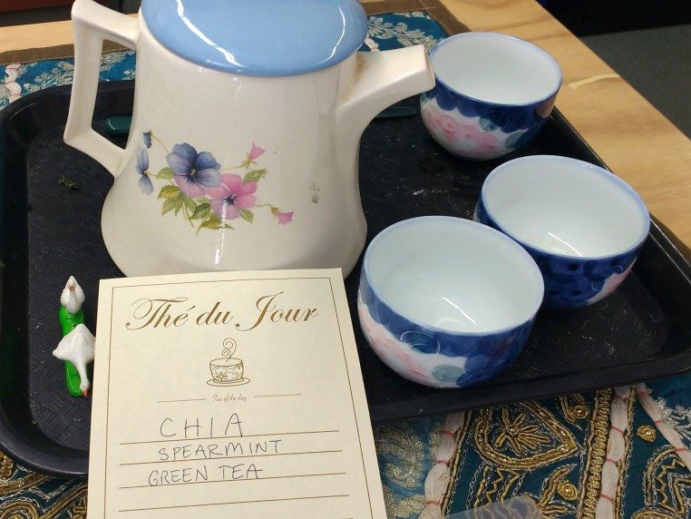 "teapot and cups with a sheet labeled ""Tea of the Day"" and listing ingredients"