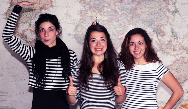 photo of Rafa, Terézia & Emilie all in black-and-white striped shirts. Emilie holds a toy figure of a mime in a striped shirt over Terézia's head