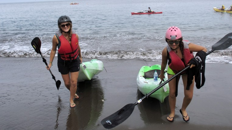 Stefanie & Zeinab drag their kayaks onto shore at Little Scorpion Anchorage, Santa Cruz Island, California Channel Islands