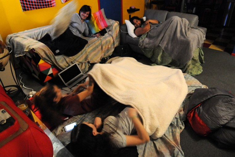 a living room filled with people sleeping on couches and the floor