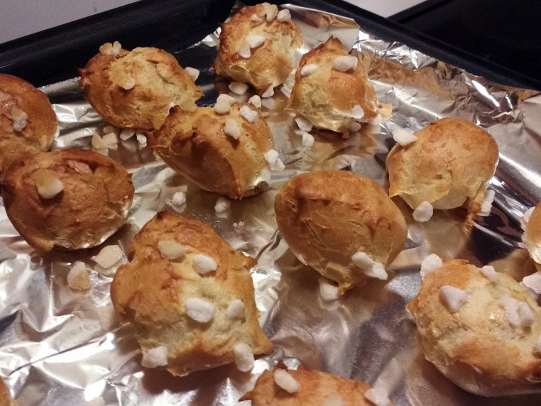 A cookie sheet filled with just-baked chouquettes