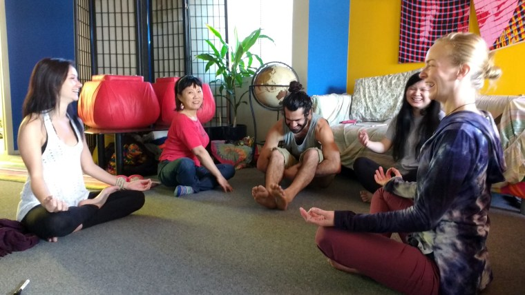Ally Snead and other students in the Runaway University dormitory lounge area beginning a yoga workshop