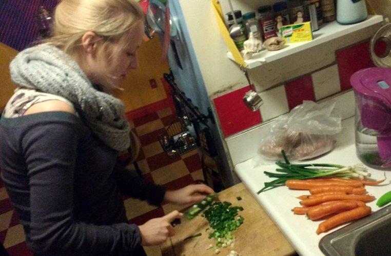Bianca chopping scallions on a cutting board