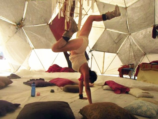 Silvana Martos doing a handstand in a soft fabric geodesic-dome-like structure at Burning Man 2012