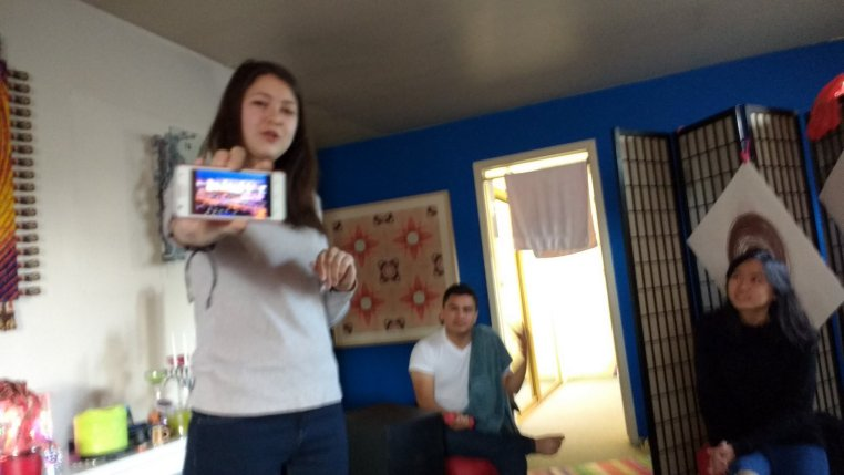 Mammetmyradova Aylar holding her phone out and showing pictures of Turkmenistan.