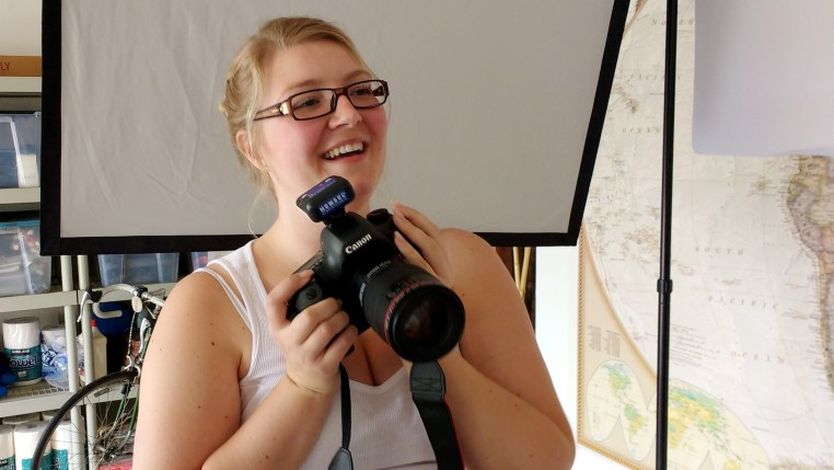 German beauty photographer Tamara Williams holding a camera and smiling big