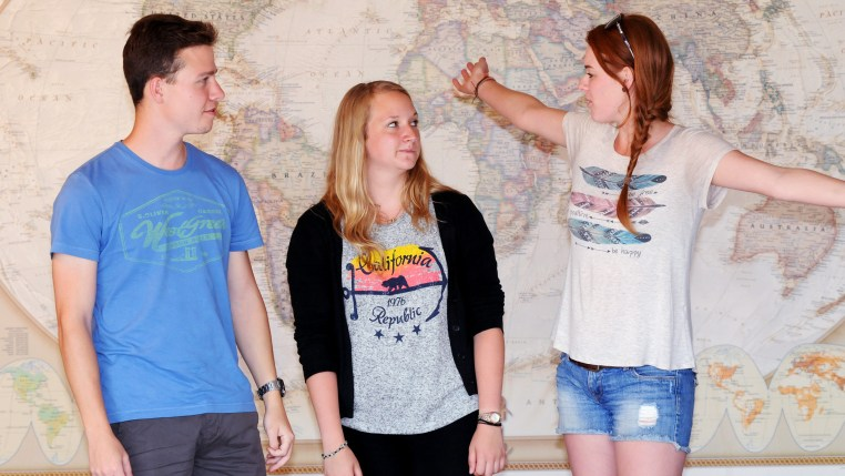 Christof Heck, Sarah Weber & Paulina Smigalski standing in front of a large world map