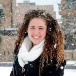 Penina Beede smiling in a city street and wearing a big coat and snow falling on her big, curly hair.
