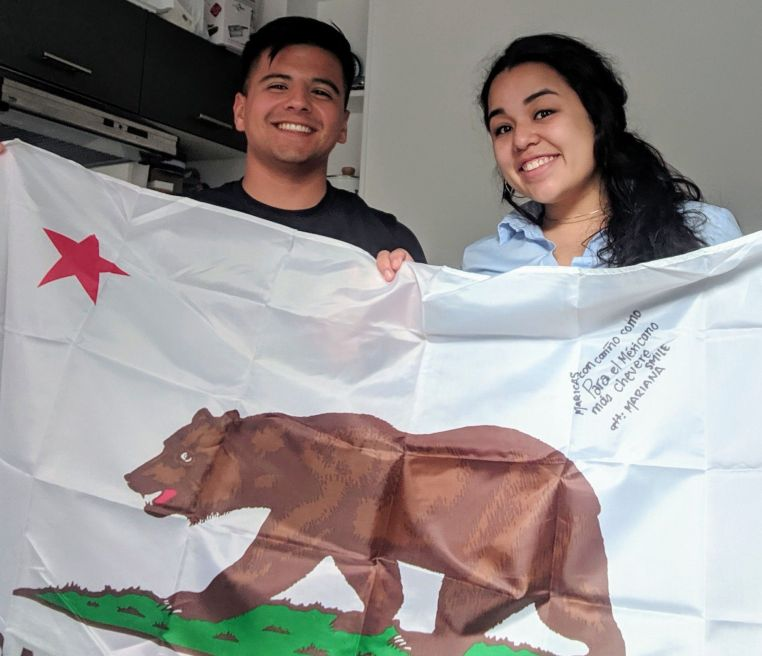 Alejandro Aregaga and Mariana holding a California flag and smiling