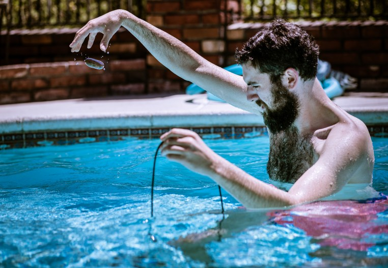Benjamin Geyer recording sounds in a pool with a hydrophone