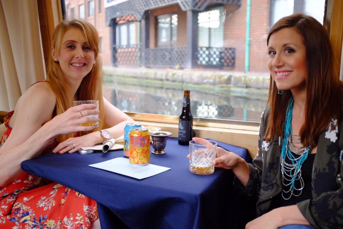 two girl.s drinking ale on a barge
