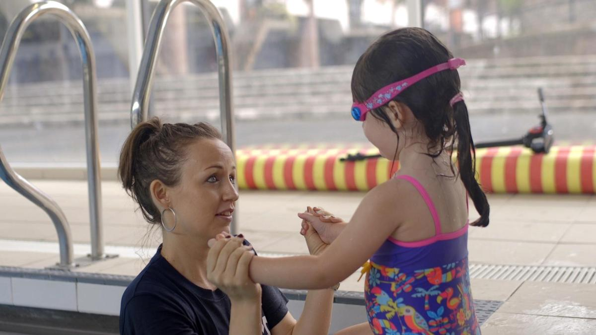 girl being taught to swim