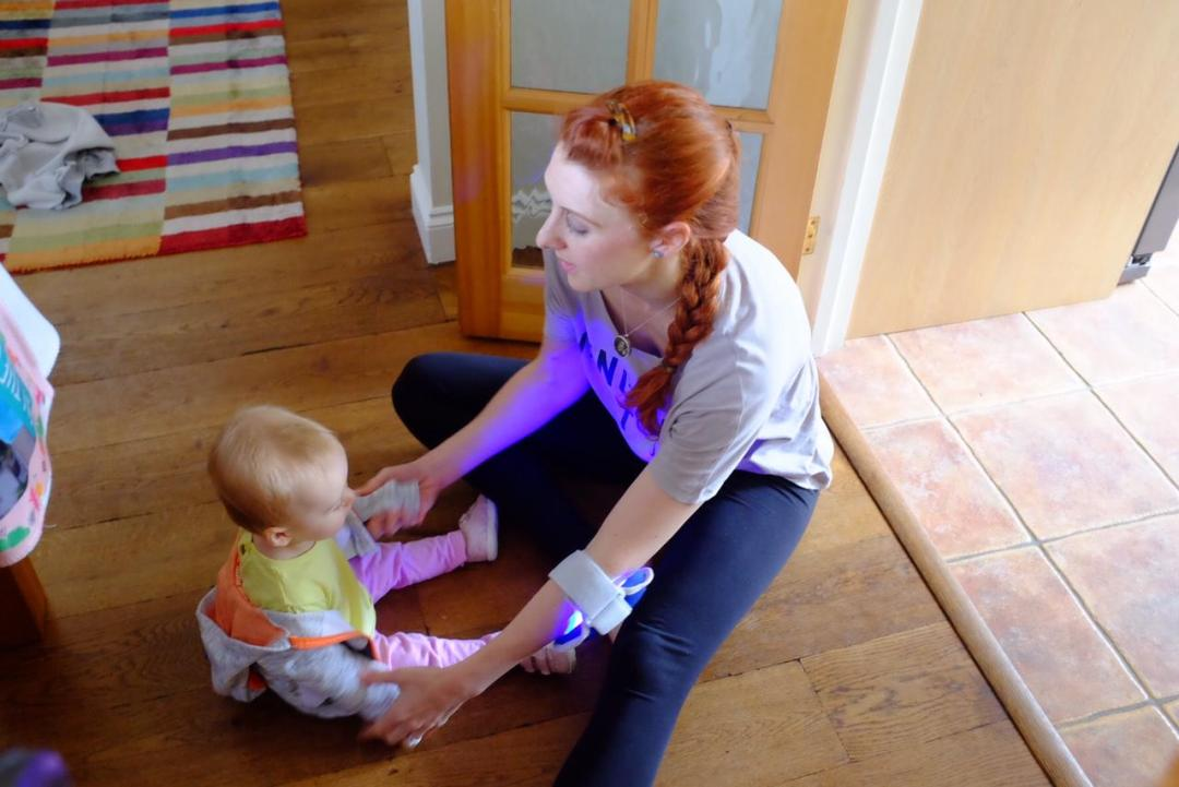 girl with baby. girl wearing philips bluecontrol on elbow for psoriasis