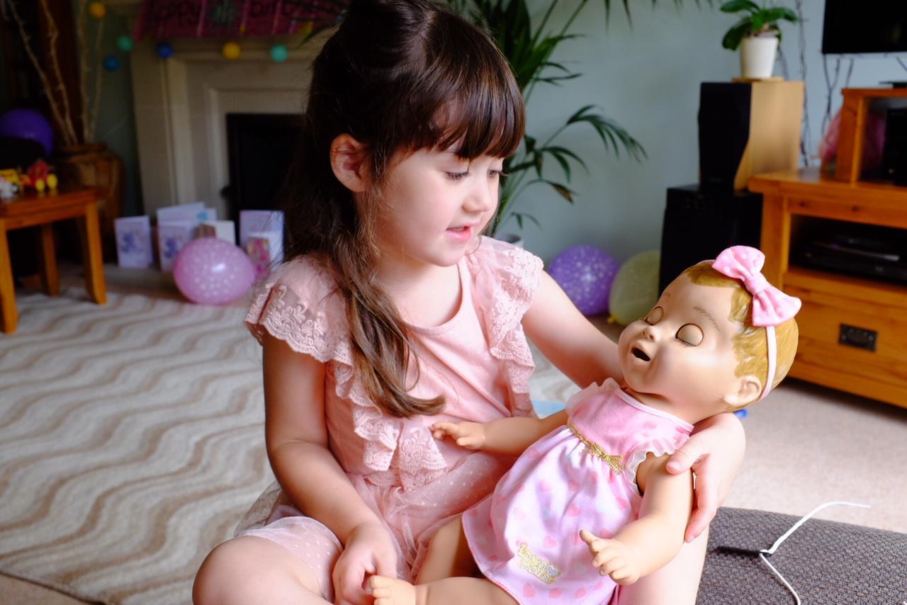 girl cuddling Luvabella doll
