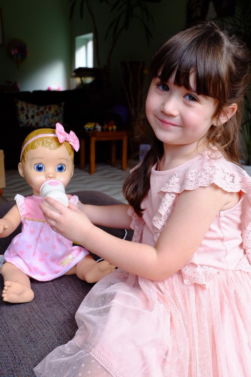 girl feeding luvabella doll with bottle