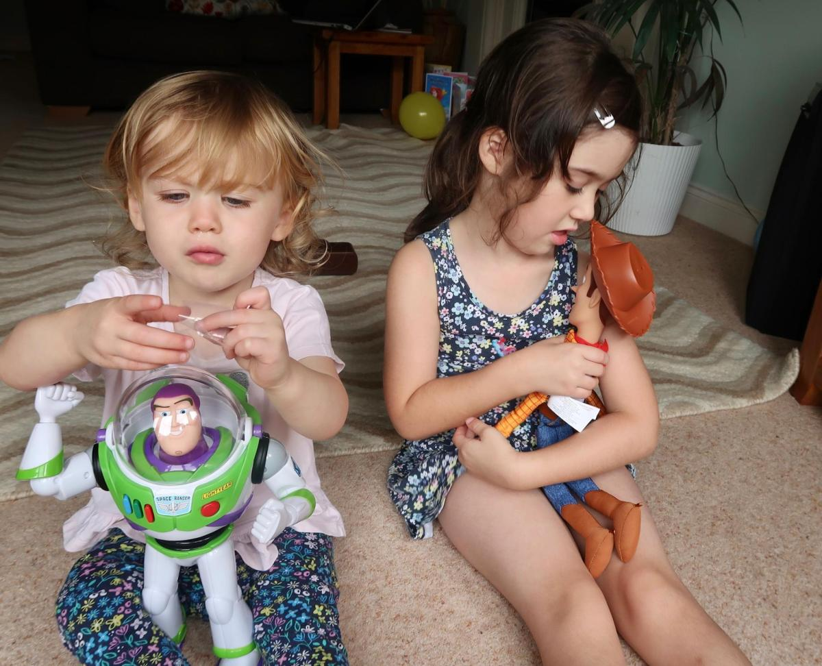 girls playing with buzz and woody