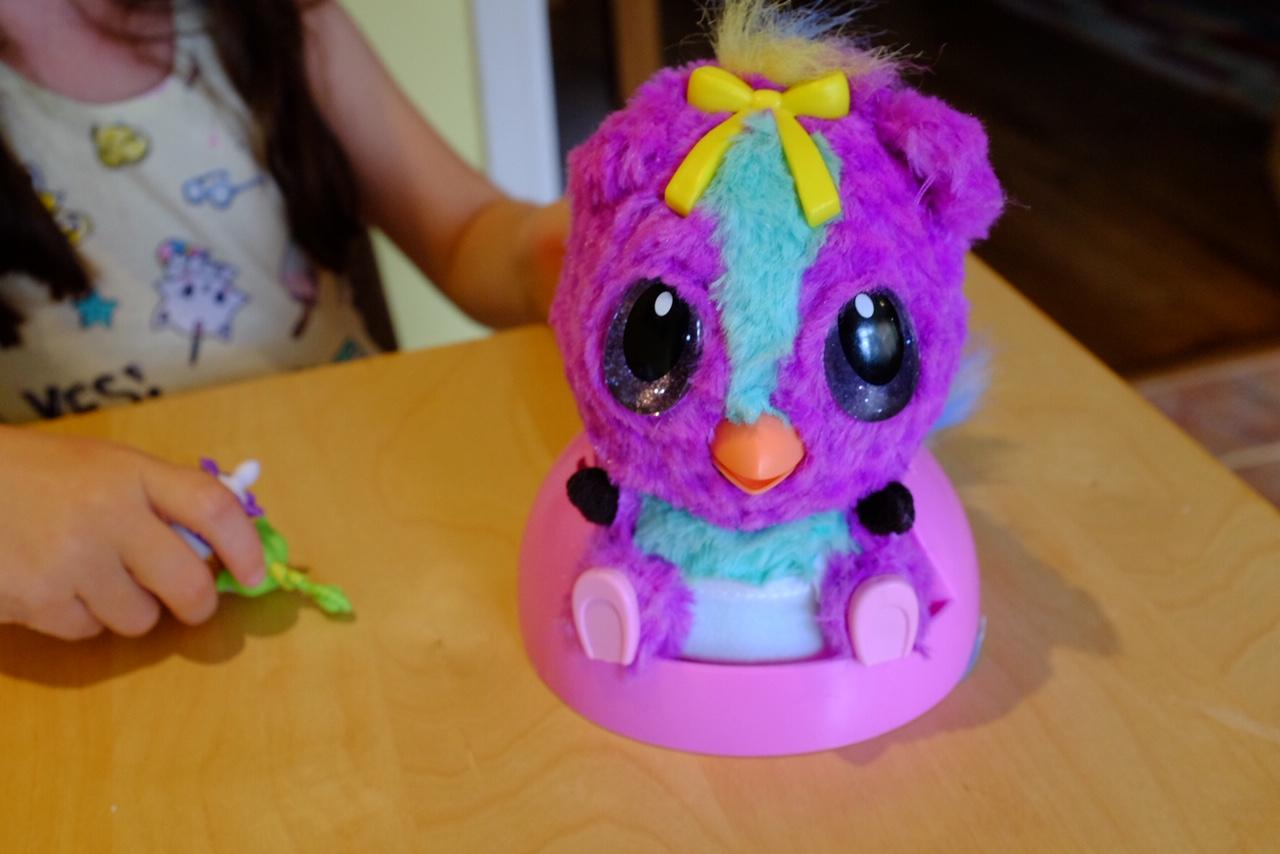Girl Hatchimals HatchiBabies is sitting in the high chair