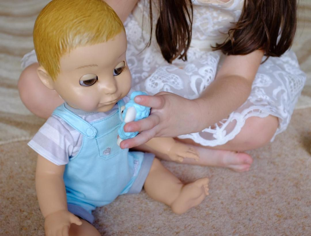 Girl playing with Lamby and Luvabeau doll