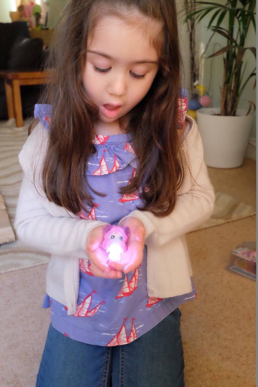 Child holding a lit up Glimmie Polaris