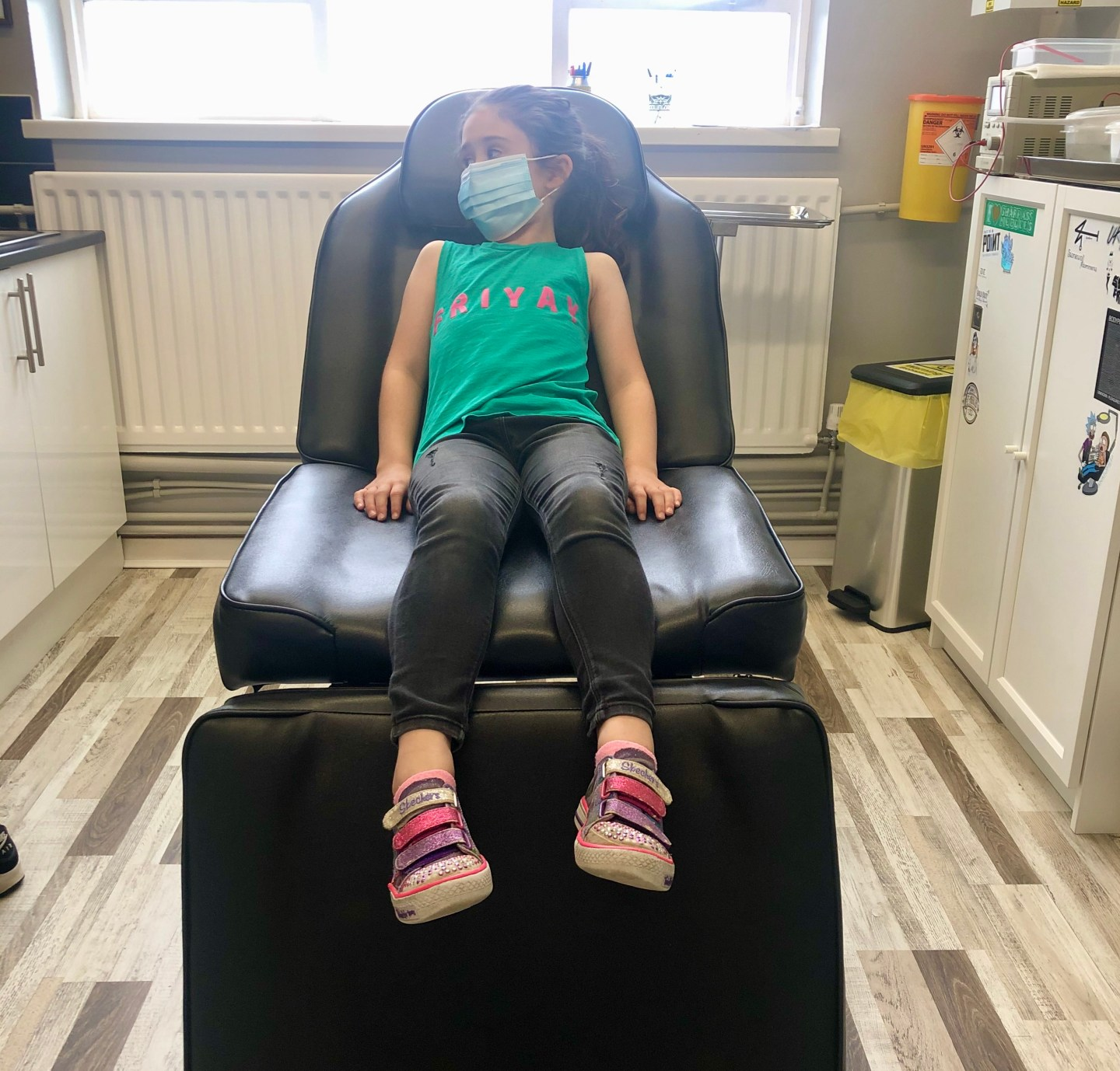 girl in chair waiting for ear piercing with a needle