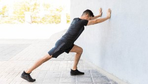Young man pushing against a wall, doing a calf stretch