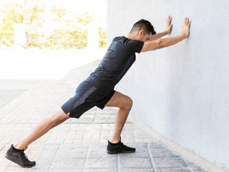 Young man performing calf stretch leaning against wall