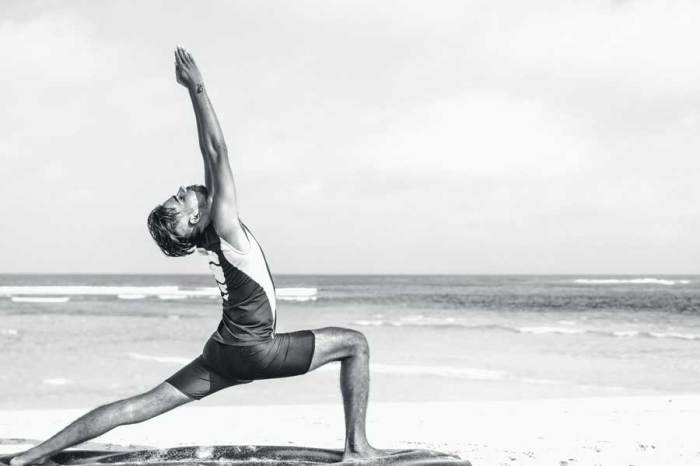 yoga άνδρας πρακτική στη παραλία και την θάλασσα