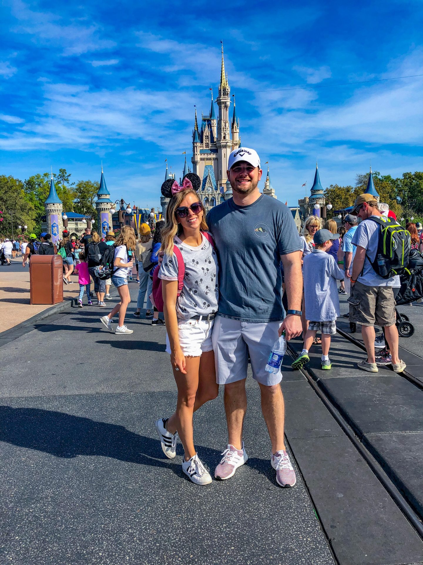 Adult Guide to Disney World Theme Parks Broken Down by Park | Running in Heels | A couple stands in front of the castle in Magic Kingdom wearing casual summer looks with minnie mouse ears.